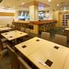 鳥料理 有明 - 内観写真:天井の高い広々とした空間にゆったりとしたテーブルの配置のオープンキッチンの店内です