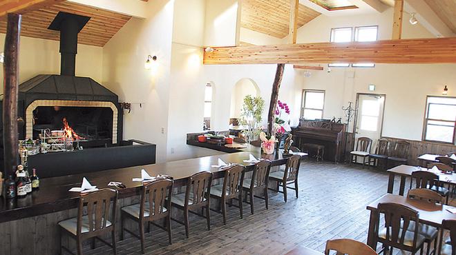 ターシャ - 内観写真:暖炉を中心としたオープンキッチンです。吹き抜けになっており開放感あふれる雰囲気です