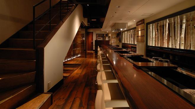 焼肉萬野ホルモン舗 - 内観写真:カウンター席は21席。カウンター内では、肉、ホルモンが次々に捌かれ、臨場感を存分にお楽しみいただけます。カウンターご利用の2名様限定で、「天王寺おまかせコース」もお楽しみいただけます。