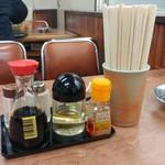 巴家 - 四人掛けテーブルばかりの店内。テーブル上に調味料受け。町中華な雰囲気たっぷり