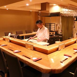 板場の熱気伝わる、秋田杉一枚板コの字カウンターでお出迎え。