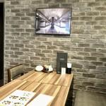 ギョウザ オウショウ - 柔らかな間接照明の入ったアーチの天井と白と黒を基調にした細長い店