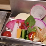 103927440 - ①サラダ&胡麻のふわふわドレッシング                       彩り豊かな野菜達が錫の器に入って配膳。                       器の下に氷を敷いて温度を保つ仕組み。                       カウンターの改造費、掛けてますねぇ。                       ドレッシングの食感が楽しいし、野菜も美味しい!