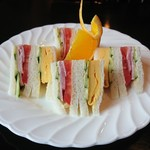 魔愁 - 【ミックスサンドイッチ】 オレンジの飾り切りが花を添えています。