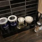 104758276 - 卓上の調味料。ブラック・ホワイトのペッパーと、こちらオリジナルのゆず酢とサカナコショー。