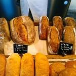 関次商店 パンの蔵 風土 - 大きな田舎パンはハーフで500円(税込)。右上のパンは何でバナナ缶と言うのかな。