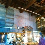 関次商店 パンの蔵 風土 - 奥のパン工房への出入り口の上には煉瓦色のタイルらしきものが。フランスっぽい?リースが下がっていました。