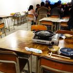 ジンギスカン専門店 羊狼館 - 食卓は学校の教室にあるようなデスクと椅子です。