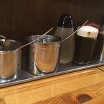 やったる -  卓上。手前から豆板醤、ニンニク、酢、醤油?、ラー油、胡椒。