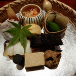 107961833 - 桜海老,チーズの醤油漬け,ウニ豆腐,身欠きにしん,子持ち昆布,マナガツオ,滋賀産赤こんにゃく,煮ごぼう