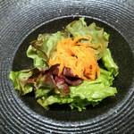 108058453 - カレーには野菜サラダ付き、レタスの上には岩塩やオイルなど爽やかな酸味の人参サラダが