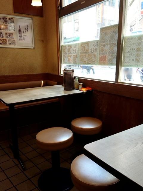 ラーメン王 後楽本舗  - 通り沿いの明るいテーブル席。
