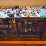 酒の宿 玉城屋 - 食事会場(酒瓶やグラスが並んでいます)