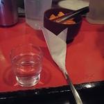 辛口料理 ハチ - 紙ナプキンを巻いたスプーンと水が出てくる