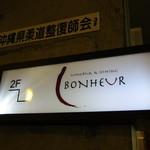 ボヌール - ビルの1階にある小さな看板