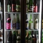 地酒蔵大阪 - 座ってるテーブル席の横には日本酒がめっちゃ並んでます