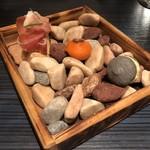 112225991 - 3種のスナック。海辺の小道を散策しているような小石にのせられたグリッシーニ、バーニャカウダ、アマレッティ。遊び心満載。