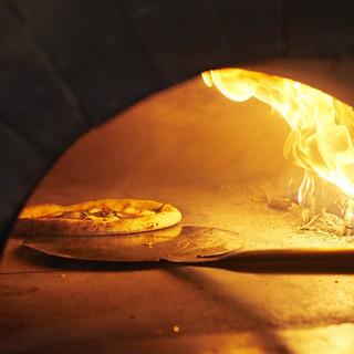 薪のみで焼き上げるピザが当店の自慢です