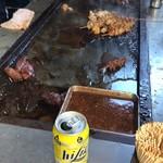 やまき - チューハイ(缶)越しに焼き場、手前のパットはつけダレ、コーナーにはキモ・アブラ用の串