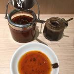 113835308 - 薬味                         唐辛子入りの辣油をよく混ぜて                         黒いのは焦がしにんにく