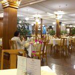 日光金谷ホテル - メインダイニングの様子。4人掛けテーブルが並び、レモンイエローのテーブルクロスが印象的