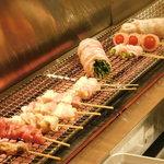 博多焼き鳥・野菜巻き・もつ鍋 かつぎや - 串焼きと野菜巻きを焼いているところ