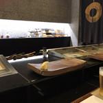 寿司割烹・難波 - 落ち着いた店内、奥に包丁の数々