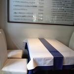 トラットリア チェーロ - 一番奥の4人掛けのテーブル席です。 白のテーブルクロスに白い椅子です。