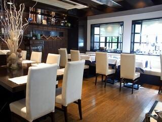 トラットリア チェーロ - 店内の雰囲気です。 入口から入って右手方面を撮っています。 木目調の調度品がいい感じですね。 そして、白い椅子が高級感をかもし出しています。