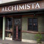 エノテカ・アルキミスタ - お店の外観です。 頭上に、ALCHIMISTAって、ドーンって大きく書いてありますね。 茶色の看板にグリーンの壁になっています。 パッと見た感じでは、イタリアンのお店に見えませんね。