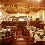 ピッツェリア ラポルタ - 天井から吊るされたワインの空き瓶や壁の絵皿など、イタリアの片田舎を思わせる温かみを感じる内装