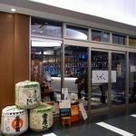 試 - お店の外観です。 全面ガラス張りになっています。 中の様子がよく見えますよ。 沢山のお酒が並んでいるようです。 店前には、樽が飾ってありますね。
