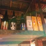 うな串 焼鳥 う福 - カウンター上のスペース有効利用の酒棚。