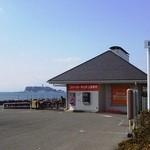 11886330 - ファーストキッチンと後方の江ノ島