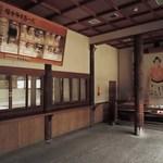 味司 野村 - 拝殿横にある御守などを授与する授与所だよ。なぜか、お相撲さんのパネルがあるね。