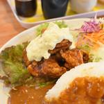 119909532 - カリッと上がった鶏肉に濃厚な甘酢が絡み、タルタルソースが乗っています。右奥にはキャベツの千切り。