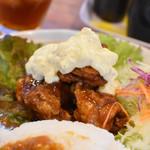119909545 - カリッと上がった鶏肉に濃厚な甘酢が絡み、タルタルソースが乗っています。右奥にはキャベツの千切り。