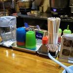 らーめんラブル - 妙にカラフルな水コップと調味料入れ。