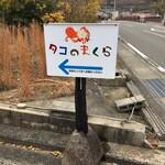 タコのまくら - 県道250号から、お店がある海岸の方へ曲がるところに置かれている案内看板です。