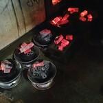 123773476 - 店員さんがストーブから真っ赤な炭を取り出して、七輪をセッティングしていました