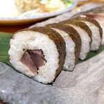 土佐清水ワールド - 土佐巻き寿司。カツオのたたきが巻かれており、スライスされた生ニンニクが絶妙なアクセント
