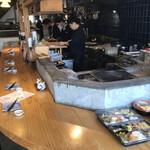 丸秀鮮魚店 - 調理中の男性スタッフ
