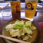 屯所 - 「生ビール中(550円)」と、串物置き皿に載せられたお通しの「キャベツ」