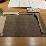 130879729 - ランチで訪問。カウンター席に座ると、席にはランチョンマットの上にスプーンや箸がセットされてました。