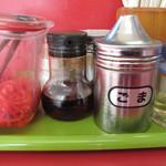 再来軒 - 卓上には豚骨ラーメンの必須アイテム。紅ショウガ・ゴマ・コショウ。