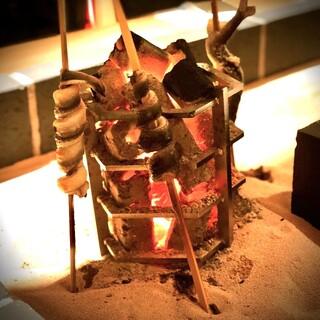 カウンター席の目の前で炭火で調理される旬の食材