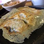 こんがりきつね - 料理写真:羽根付のこんがり餃子。熱々の鉄皿で提供。