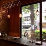137361601 - 通りに面した大きな窓と照明が印象的なカウンター席(オープンキッチンで調理の様子が見える)