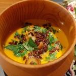 138093415 - まろやかで深みある南瓜スープに、カレー風味でソテーしたミニあさりや原木椎茸、程よい苦味のカカオニブがアクセント