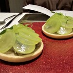 138924112 - 【アミューズ】 秋刀魚 シャインマスカットのスライスが美しく彩る一皿目は、下に秋刀魚のタルトを忍ばせています♪